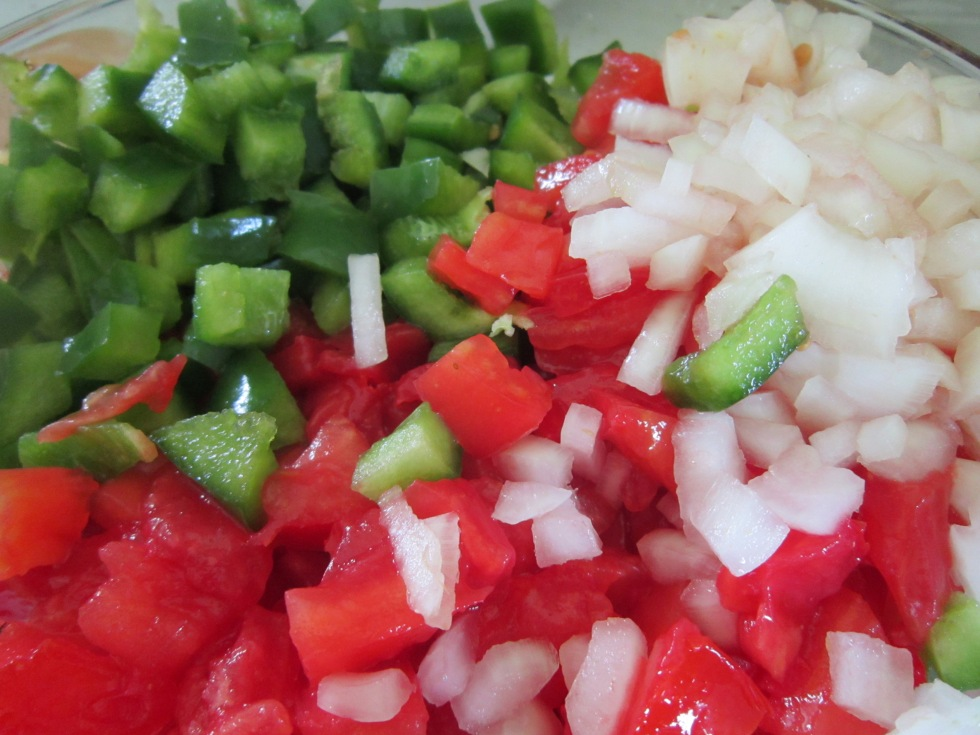 Mixing tomatoes, onion, and green pepper..